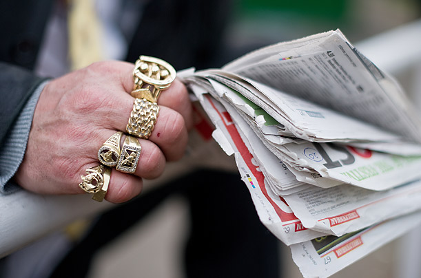 A spectator wears horse racing-related jewellery on his fingers at the