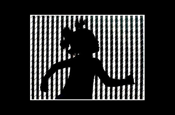 Jade Marine, 3, is silhouetted against a fence as she skips along in New Kensington, Pa.