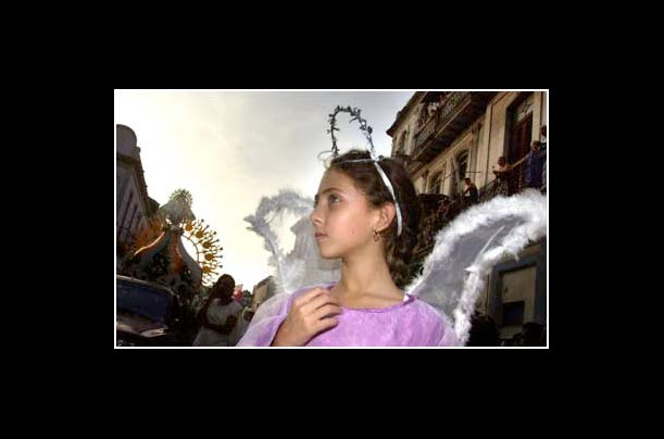 A girl dressed as an angel joins a procession for the Virgin of Charity, the patron saint of Cuba, in the streets of Havana
