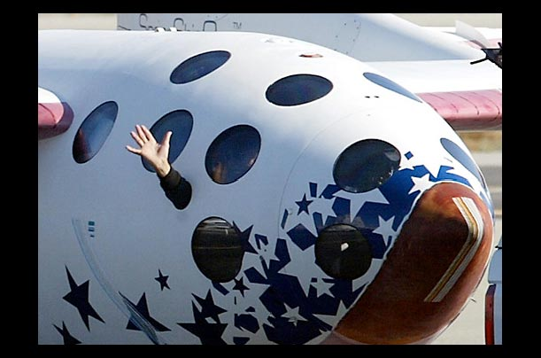 Pilot Michael W. Melvill waves from the window of SpaceShipOne while being towed after a successful landing