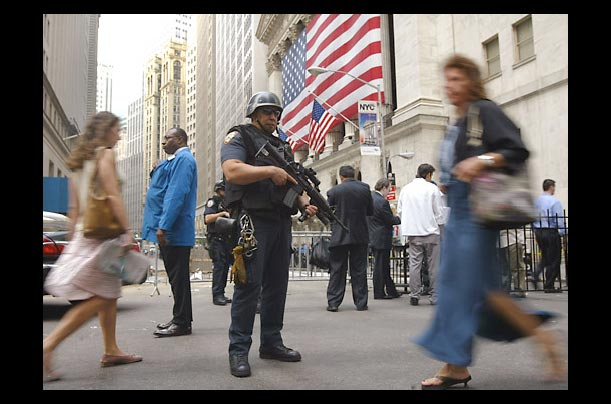 an armed nypid offier guards the new york stock exchange from terrorist attacks