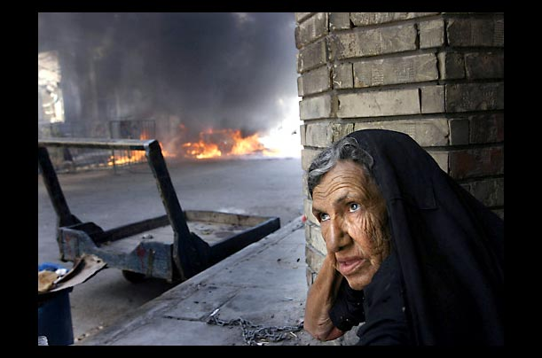 A woman sits in front of a burning car near the shrine of Imam Ali in Najaf, Iraq