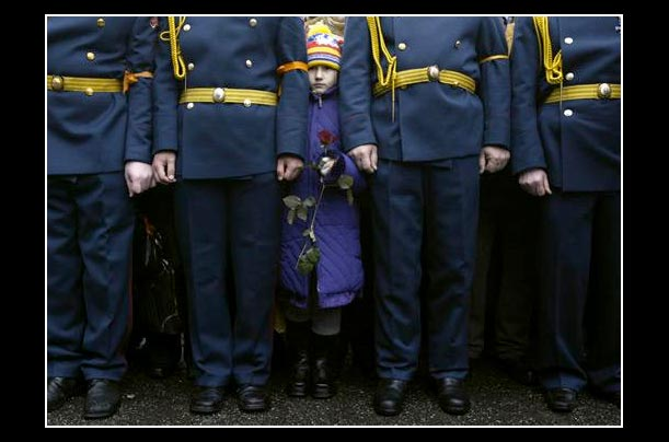 a little girl peeps through a rank of cossacks, supporters of viktor yushchenko during a rally