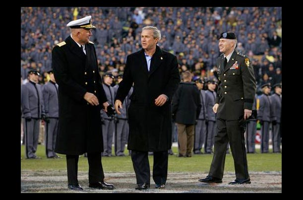 Vice Admiral A. Rodney Rempt, Superintendent of Annapolis, and Lt. General William Lennox, Superintendent of West Point, exchange looks as President George W. Bush walks across the field at the Army-Navy game at Lincoln Financial Field in Philadelphia