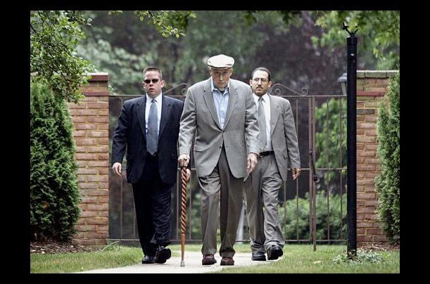 Supreme Court Chief Justice William H. Rehnquist is escored by security at his home in Arlington, Virginia