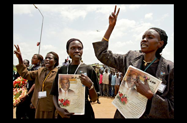 Sudanese women carry portraits of former rebel-turned Vice President John Garang during his funeral in Juba