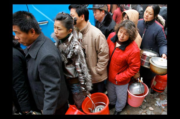 residents from Harbin, Heilongjiang Province, northeast China queue for water after a toxic Benzene spill in the Songhua River