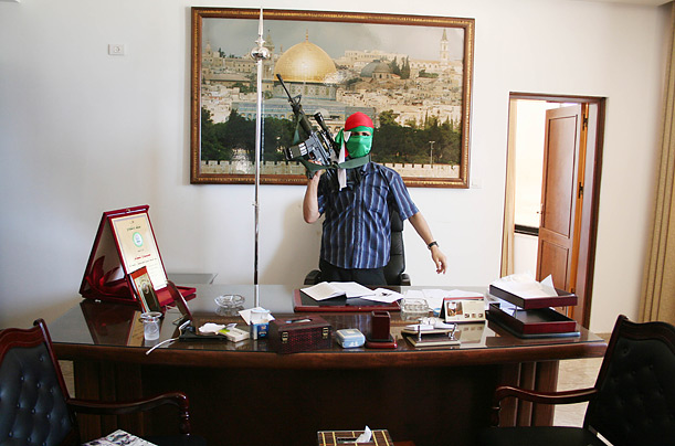 Hamas fighter sits at Palestinian president Mahmud Abbas's desk in the president's Gaza