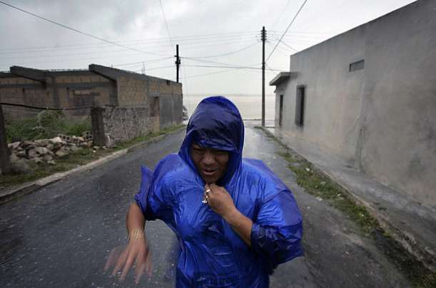 A woman covers herself with a plastic poncho while walking in heavy rains in Sabancuy, Mexico, in the Yucatan peninsula, as Hurricane Dean swept through Mexico.