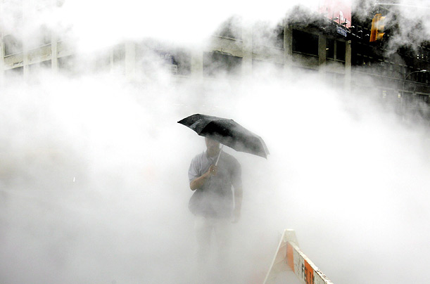 A man with an umbrella walks through steam rising from a construction site during a rain storm in New York.