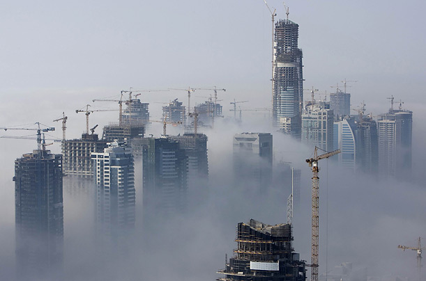 Morning fog rolls into the Dubai marina, where construction is underway on three man-made islands and the world's tallest building.
