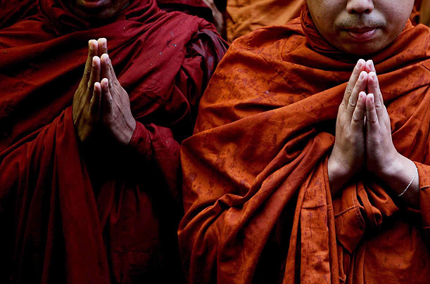 Buddhist monks pray during heavy rain outside the Union of Myanmar Embassy in Mayfair, London, in a show of support for the protests by Buddhist Monks in Burma.