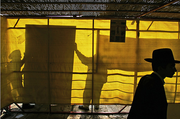 An Orthodox man walks inside a Sukkah near the Tomb of the Patriarchs, in Hebron, during Sukkot, a holiday commemorating the Jews' 40 years of wandering in the desert.