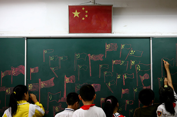 Students draw the Chinese national flag on a chalkboard during an activity to mark National Day, Sept. 30, 2007, in Nanjing.
