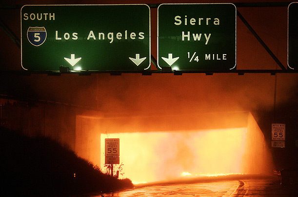 A fire burns from within a tunnel at a multi-vehicle crash on the Interstate 5 and Interstate 14 freeways north of Los Angeles.