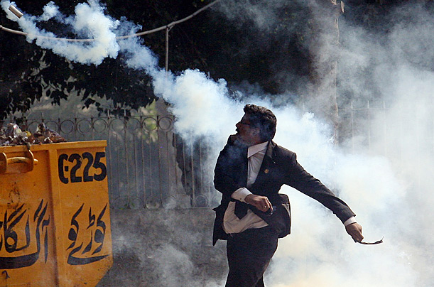 Pakistani lawyer throws a tear-gas shell back towards the police in Lahore during a protest against the state of emergency declared by President Pervez Musharraf.