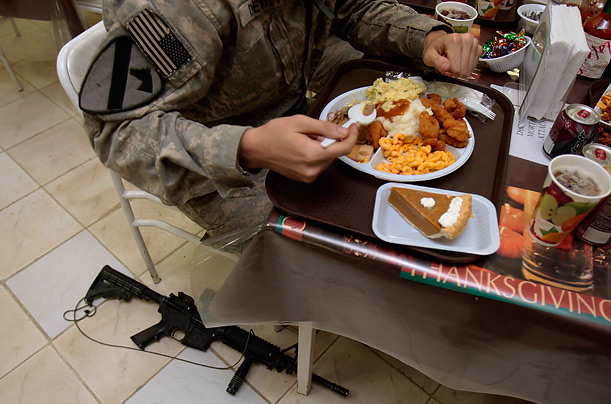 A soldier eats with his weapon close at hand during a Thanksgiving dinner at Forward Operating Base Rustamiyah, Iraq.