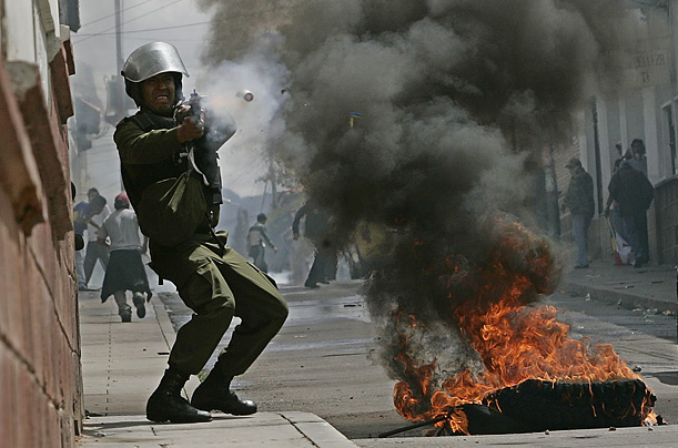 A police officer fires a gas canister in an attempt to quell in a protest in Sucre, Bolivia.