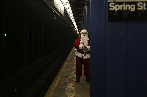 A participant in Santacon 2007 waits on a subway platform in New York City. Organized over the Internet and led by text messages