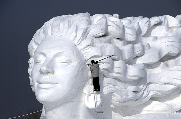 A sculptor works on the statue
