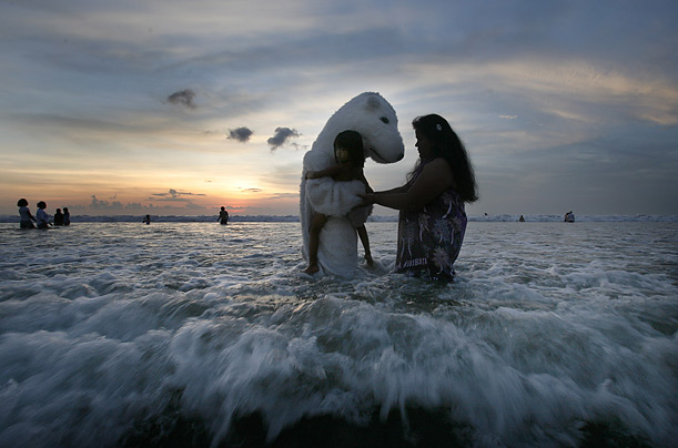 An environmental activist and a Pacific Islander pose for a photo on Kuta Beach after the end of the U.N. Climate Conference in Bali, Indonesia.