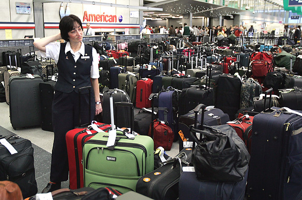 A ticket agent handles passengers' bags at Chicago's O'Hare International Airport during the crush of holiday travel.