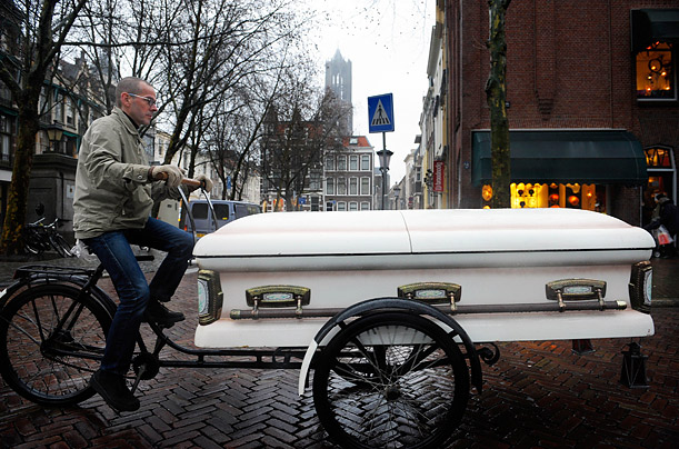 Artist Dirkje Kuik rides his coffin tricycle in the centre of Utrecht, Netherlands. The coffin is used to hold shopping purchases.