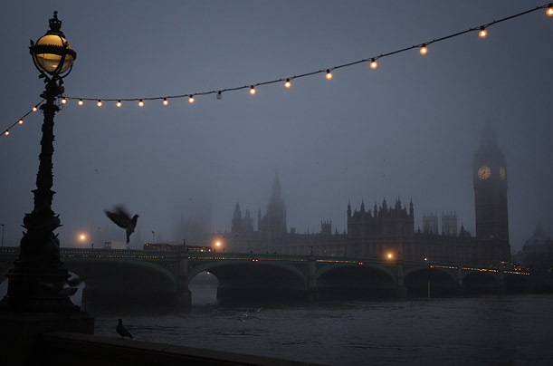 Parliament, Westminster Bridge and the River Thames are enveloped in fog.