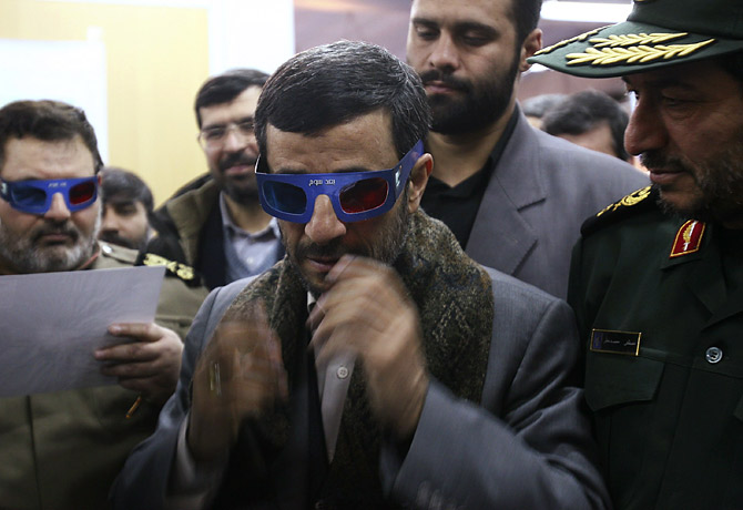 Iranian President Mahmoud Ahmadinejad cons a pair of 3-D glasses in order to view a film about the Iranian space program