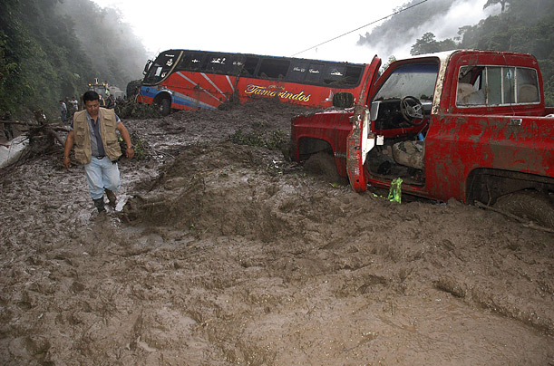 A passenger bus is trapped in debris as a journalist arrives at the site of a mudslide in Mancha Grande zone, Manabi province in Ecuador.