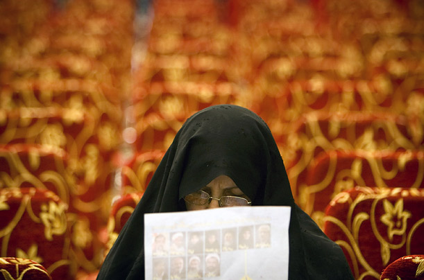 A woman looks at an electoral pamphlet at an election campaign rally in Tehran, Iran. Iranians will go the polls on March 14.