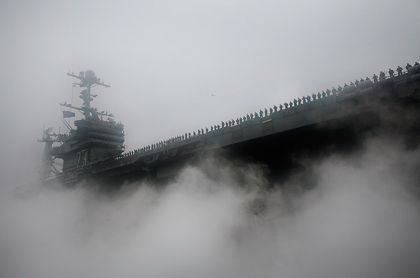 Sailors line the flight deck of the USS George Washington as it prepares to depart to its new station in Yokosuka, Japan.