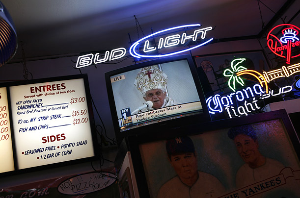Pope Benedict's Mass at Yankee Stadium is broadcast on a television in a bar in the Bronx.