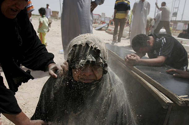 A woman grieves for her son, Ayad Hafidh, as he is buried in the Shiite holy city of Najaf, south of Baghdad, Iraq.