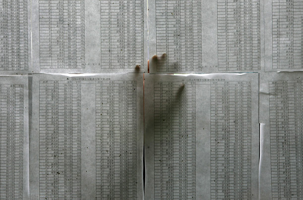 A relative scans a list of high school students who survived the powerful earthquake, at a stadium in the city of Mianyang, China.