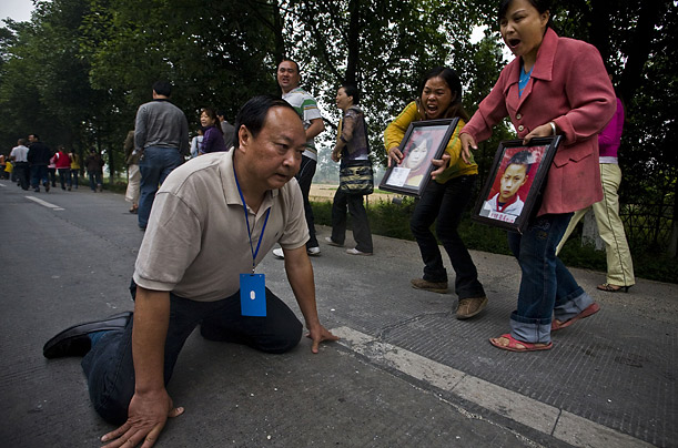 Jiang Guohua, the Communist Party boss of Mianzhu city, Sichuan province, kneels on the ground before angry parents whose children were killed by school collapses in the earthquake, pleading with them to stop their protest march