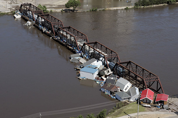 Boat houses from the Ellis boat harbor and other debris are smashed against a railroad bridge near the Timecheck neighborhood near Cedar Rapids, Iowa.