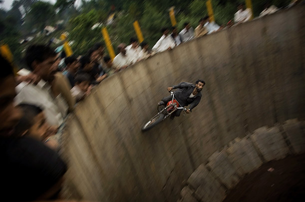 An acrobat rides his motorcycle around a circular track during a memorial to the Muslim saint Syed Lal Shah, near his shrine in Muree, Pakistan.