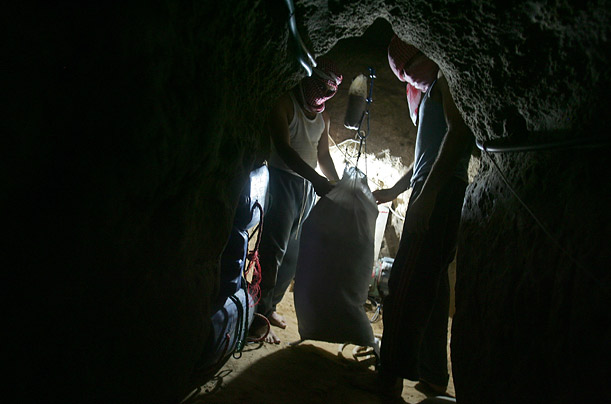 Palestinians pull a sack of smuggled goods through a tunnel that runs from Egypt to the Rafa refugee camp in Gaza.