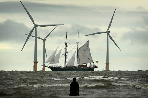 A Tall Ship sails past the Burbo Bank windfarm on the approach to the Port of Liverpool in England. One hundred vesselsracing festival