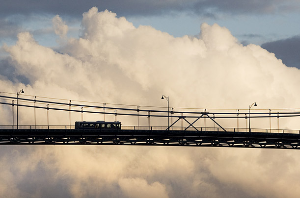 city transit bus is silhouetted against evening clouds as it crosses the Lions Gate Bridge into downtown Vancouver, British Columbia