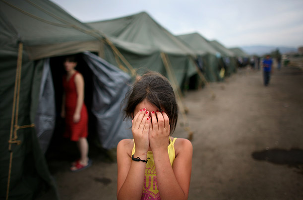 A young Georgian refugee covers her eyes at a refugee shelter in Tbilisi, Georgia