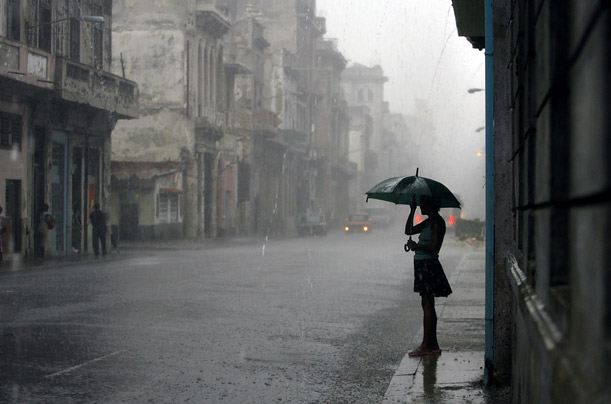 A woman covers herself from heavy rains caused by approaching Hurricane Gustav in Havana, Cuba.