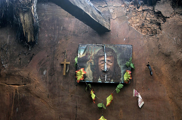 A damaged portrait of Jesus Christ hangs on the wall of a demolished home after an anti- Christian mob attacked it in Barakhama village in the eastern Indian state of Orissa