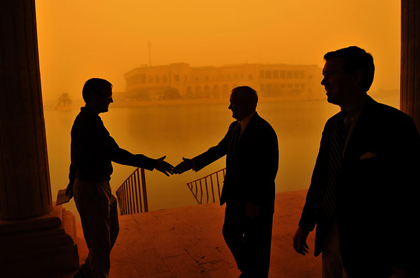 With a sandstorm blowing behind him, Defense Secretary Robert Gates greets a reporter on his way to a television interview at Camp Victory in Baghdad.