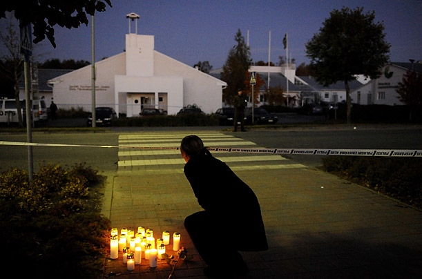 A girl places a candle in front of the Kauhajoki vocational high school in Finland, where a gunman shot and killed 10 people before turning the gun on himself.