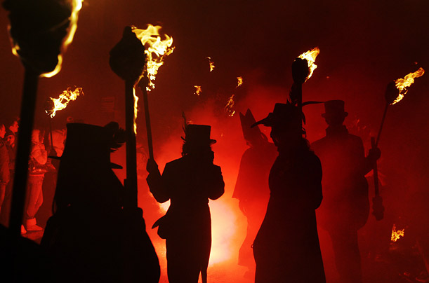 Torch-bearers walk through the streets of Lewes, England on route to Bonfire Night festivities, part of the celebration of Guy Fawkes Day.