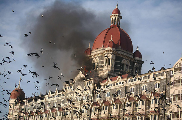 Pigeons fly near the burning Taj Mahal hotel in Mumbai, where Indian commandos battled on with armed Islamist militants to free hostages.