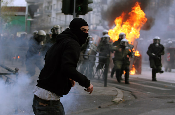 Youths clash with riot police during a massive demonstration near the main police station in Athens following the deadly police shooting of a fifteen-year old boy.