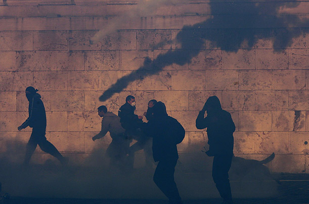 Protesters run through tear gas during riots in Athens, Greece.